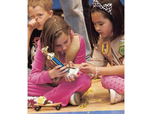 Y-Guides Hopi Tribe member Isabella Eng, right, 6, admires Courtney Jones' trophy for first place in the third-grade division. Eight-year-old Jones won with her SpongeBob SquarePants riding a surfboard entry.