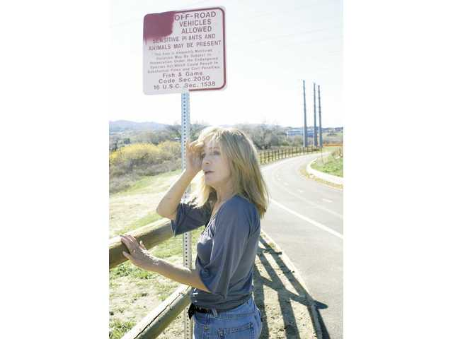 Local environmentalist Teresa Savaikie looks out over the Santa Clara River near McBean Parkway in Valencia Saturday, next to a vandalized sign which prohibits off-roading in the river bed.