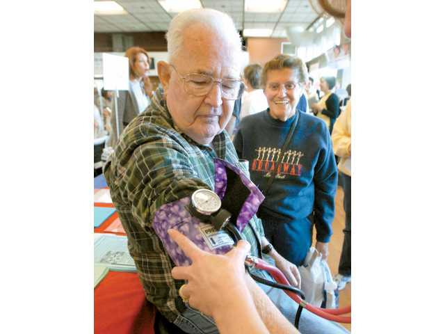 Bob Phelan gets his blood pressure checked as his wife, Virginia, looks on Saturday during the Health and Wellness Fair hosted by the Santa Clarita Valley Chamber of Commerce at College of the Canyons.