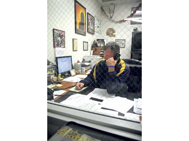 College of the Canyons head football coach Garett Tujague makes phone calls in his office on Friday. Tujague and the rest of his staff send around 23 football players to four-year programs on scholarship every year.