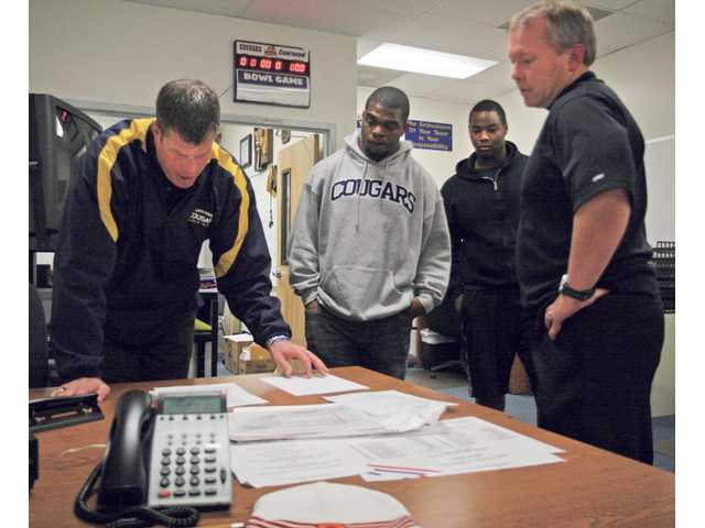 From left to right, College of the Canyons head football coach Garett Tujague, COC linebacker Evan Harrington, Cougars offensive lineman Louiszell Alexander and University of Colorado defensive coordinator Ron Collins go over paperwork in Tujague's office at COC on Friday. Harrington will play for Colorado next season, while Alexander will head to Syracuse University.