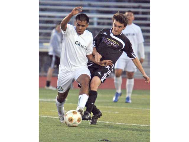 Canyon's Sipriano Vigil (23) battles Valencia's Robby Bruza for control of the ball Monday at Canyon High School. The Cowboys claimed sole possession of first place in the Foothill League with a 1-0 win.