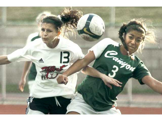 Hart's Presley Lambert (13) heads the ball toward the goal as Canyon's Nicole Guerrero defends Tuesday at Hart High. Hart won 3-1.