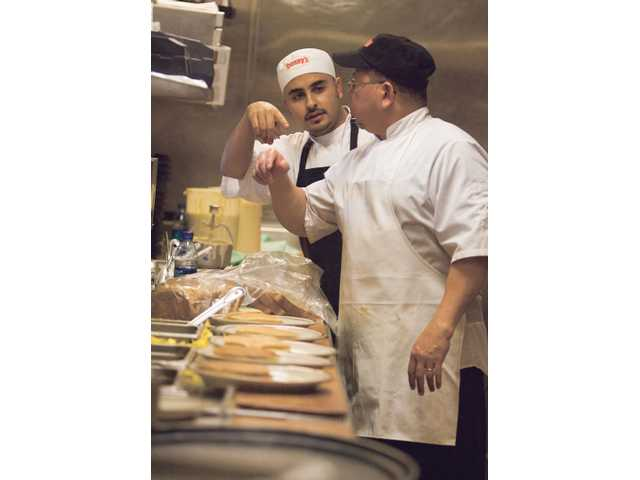 Denny's restaurant cooks Jorge Herrera and Marcel Flohr line up the plates as they prepare for an estimated 800 Grand Slam breakfasts during the restaurant's free giveaway of the meal from 6 a.m.-2 p.m. Tuesday.