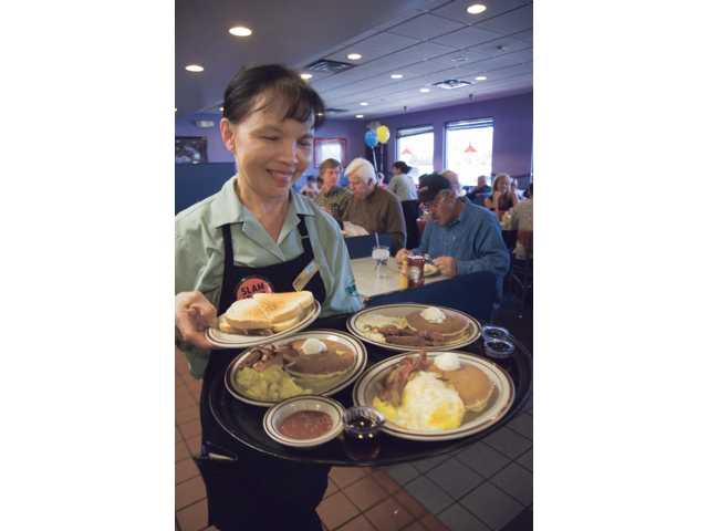 Sue Pothong, server at Denny's restaurant, walks with a tray full of Grand Slam breakfast as she, along with her coworkers at the Valencia Denny's, served from 6 a.m.-2 p.m. Tuesday. Denny's advertised the free breakfast in a commercial during Super Bowl Sunday.
