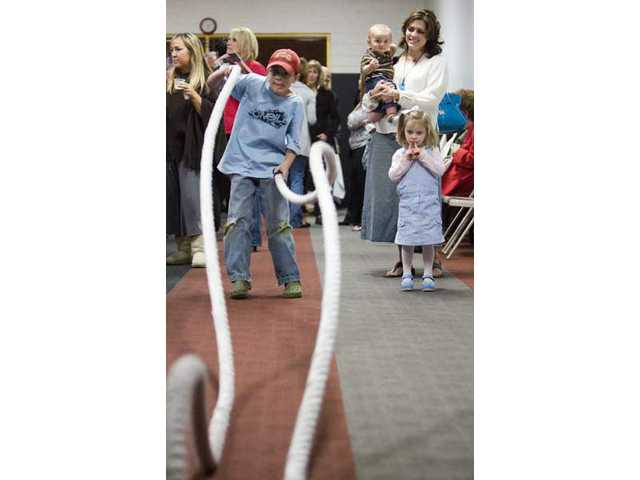 Mother Cheralyn Goeckeritz, nine-month-old Thomas Goeckeritz and Eliza Goeckeritz, 3, of Newhall, watch as Tyler Goeckeritz, 9, tries out an exercise routine using ropes, during the grand- reopening of the Results Fitness gym in Newhall, Thursday night. The gym, which went through a makeover, has added a Shake Cafe.