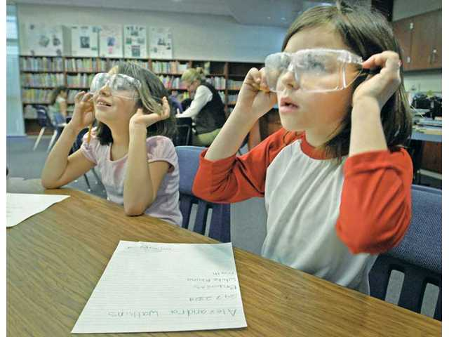Third-graders Maria Soto, left, and Lexi Watkins adjust their goggles, which have been smeared with Vaseline to imitate the vision of a person with sight impairment, as part of a disability awareness program at Emblem Elementary School on Wednesday.