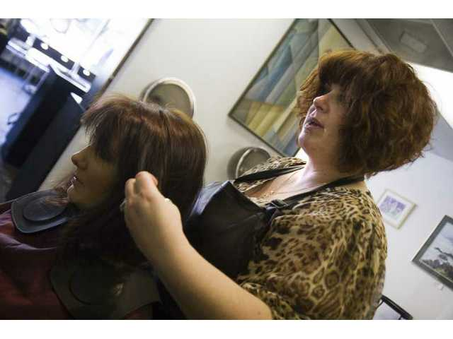 Owner and stylist of Capelli Salon, Sabina Fetter works on her client's hair Tuesday morning.