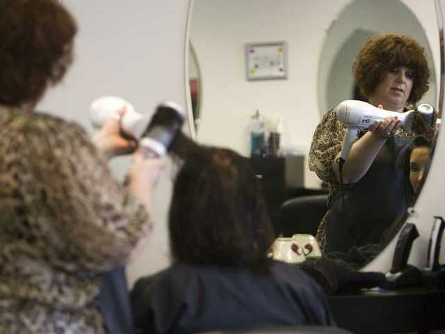 Sabina Fetter works on a client at her salon, Capelli, in downtown Newhall.