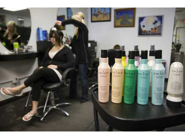Enjoy hair products are used and sold at Capelli Salon in Newhall. Erica Flint styles Ashley Rodgers hair in the background, Tuesday morning.