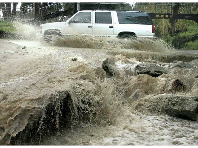 Rushing water creates a waterfall as an SUV crosses a rain-swollen creek bed on Quigley Canyon Road near Oak Orchard in Newhall after heavy rain fell on Santa Clarita on Friday morning.