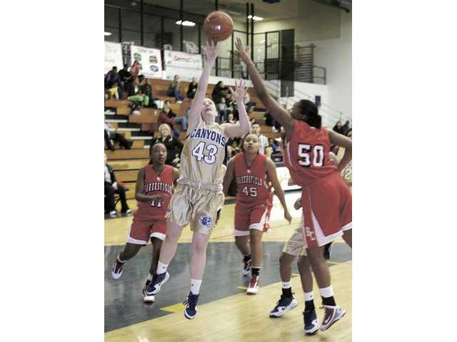 College of the Canyons forward Tera McKelvey (43) scores against Bakersfield College defenders Dianna Roseburr (11), Alexi Smith, (45) and Lakai Banks-Dean (50) on Saturday at College of the Canyons. The Cougars pushed their winning streak to 15 games with the 93-50  win over Bakersfield.
