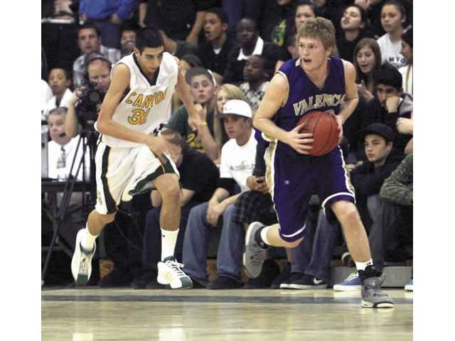 Valencia basketball player John Otavka, right, runs down court as Canyon's Ryan Snyder trails Feb. 8. Otavka was recently named to the Southern California Interscholastic Basketball Coaches Association CIF-Div. II-AA first team.