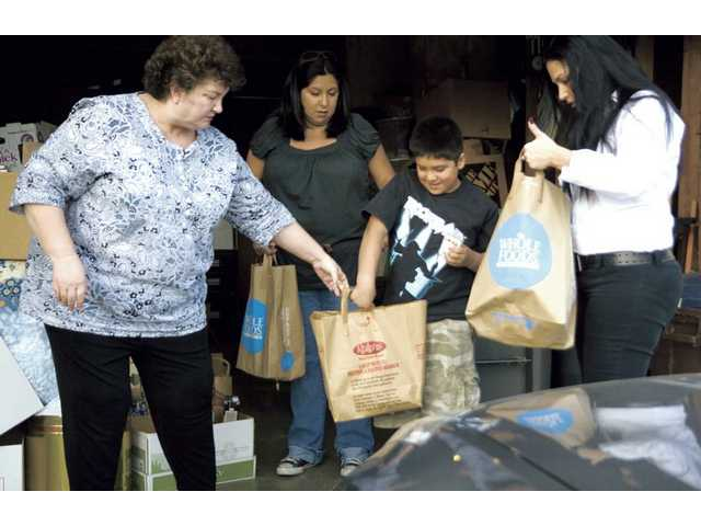 Left to right, Debbie Quick, helps Juanita Ramirez, her son Isaac Castillo-Ramirez and Laura Evora, pick out needed items. Quick is the founder of SCV Single Mothers, a support group.