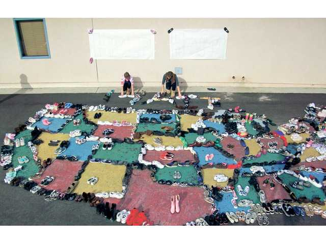 Mitchell Community School students arrange donated shoes into a map of the United States.