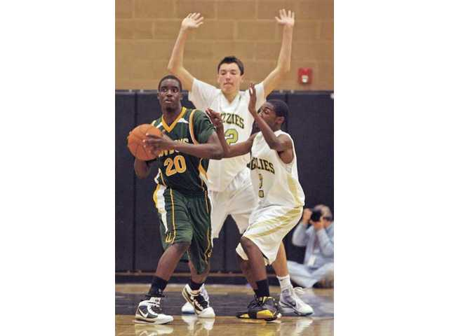 Canyon forward Brian Nnaoji (20) looks to pass out of a double-team by Golden Valley's Corey Chaisson, right, and Taylor Statham during a game on Jan. 29 at Golden Valley High School. The Grizzlies run a full-court pressure defense, while Canyon opts to play man-to-man in the halfcourt game.