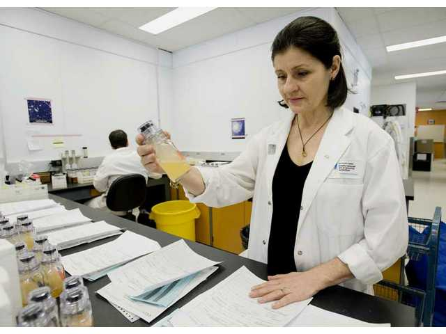 In this photo taken on Wednesday, Jan. 13, 2010, director Christiane Ayotte holds up a sample at the National Scientific Research Institute in Laval, Quebec. Canada's only permanent dope-testing facility is jammed in preparation for Winter Olympics opening ceremonies Friday.