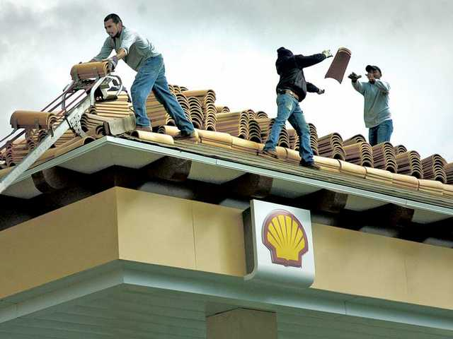 Workers toss roofing tiles as they move them from a conveyor belt onto the roof of the new Shell gas station at The Plaza at Golden Valley shopping center under cloudy skies on Tuesday in Canyon Country.