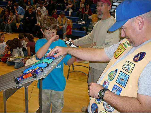 James Haight watches intently as Brady Ballentine perfectly places the cars on the track at the Santa Clarita YMCA Pinewood Derby on Jan. 25 at Saugus High School.