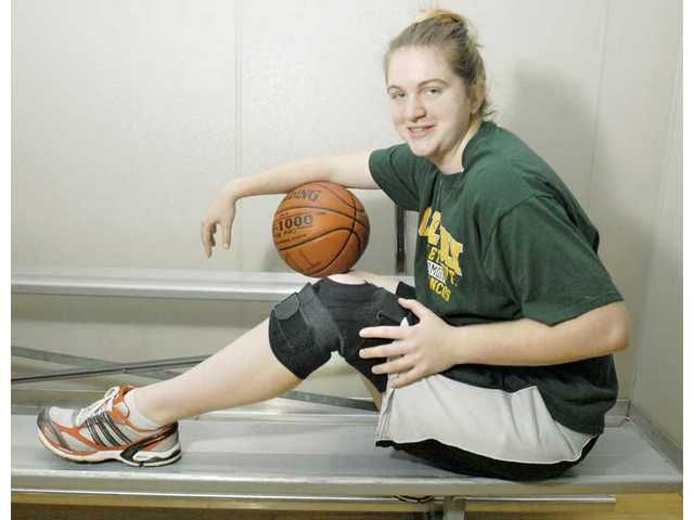 Hart graduate Megan Ford sits on a bench with her hand on top of a knee brace. Ford tore her ACL  Jan. 10.
