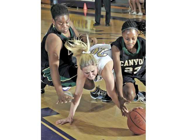 Valencia guard Lindsey Hill (20) fights for the ball with Mariah Mewborn (5) left, and Alia McCoy of Canyon at Valencia on Tuesday.
