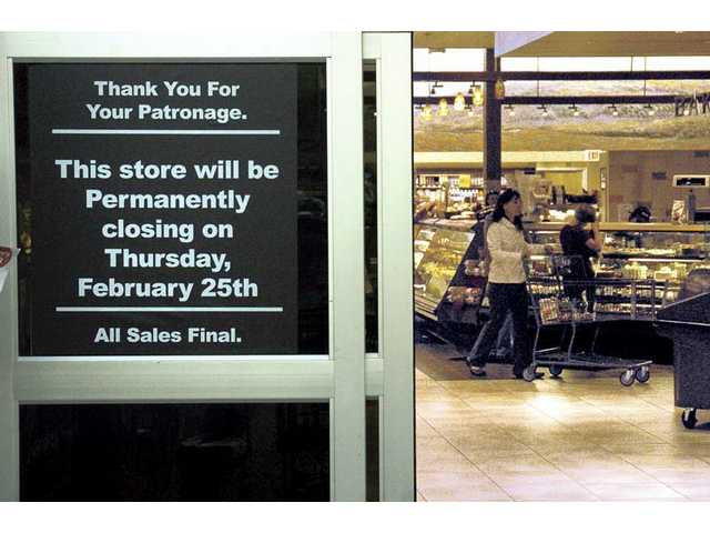 A sign posted at the entrance of the Bristol Farms store in the Bridgport Marketplace shopping center tells of the stores closing as people shop inside on Wednesday.