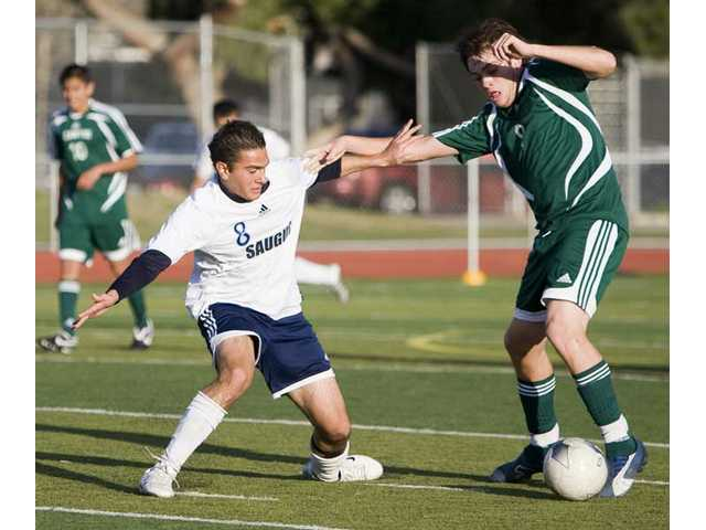 Saugus High's Amir Ranjbar-Shiraz (8) attempts to steal the soccer ball from Canyon's Juan Munoz (9) Tuesday at Saugus High School.