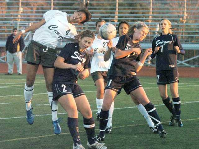 Canyon's Malaya Cabrera (4) heads the ball toward the goal as Saugus' Heather Pilch (2) and Shasta Fisher (1) defend Tuesday at Canyon High.