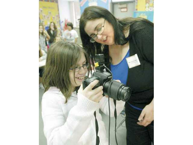 Fifth-grader Cassie Gutierrez, left, and photographer Tracey Melchiori check the pictures they have taken in a portrait set up as part of Career Day at Valencia Valley School Wednesday.