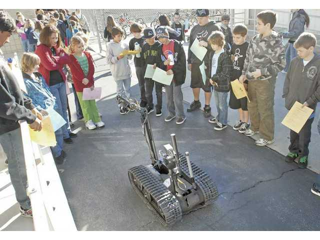 Fourth- and fifth-grade students get a close-up look at a Talon remote-control robot as it's demonstrated by a member of the LAPD Bomb Squad as part of Career Day events at Valencia Valley School, Wednesday.