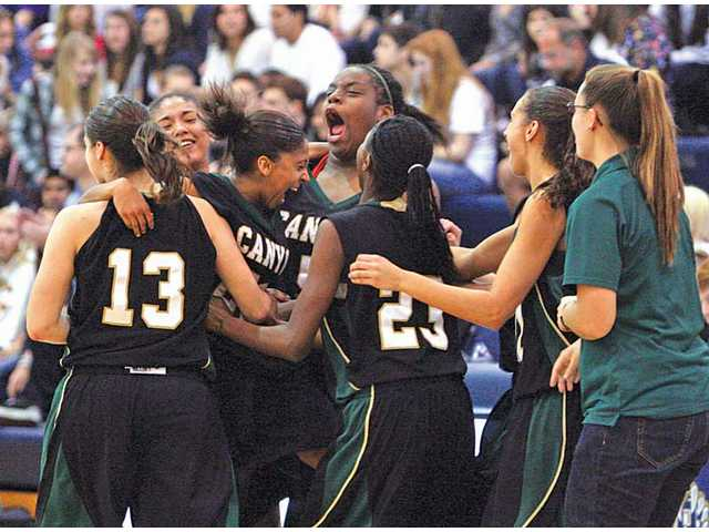 Canyon girls basketball players celebrate their 56-44 victory over West Ranch on Thursday night at West Ranch. The Cowboys won their first Foothill League girls basketball championship since 1973.