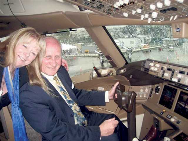 Sally Bond and Bill Wolf, of Canyon Country, in the cockpit of the new V Australia Boeing 777 after the plane's arrival at LAX Friday.