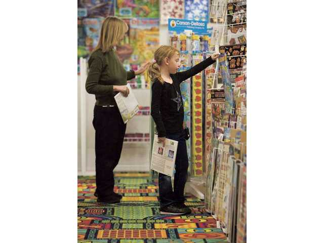 McKenzie Furie, right, helps her mom, Kelly Furie, organize A+Teaching Supplies store on Soledad Canyon Road Wednesday.