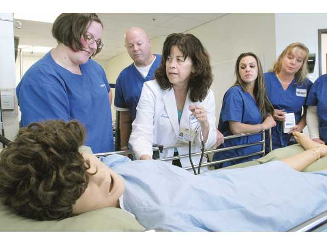 Deborah Shields, RN Instructor, center, works with a class of nursing students at Charter College on Thursday. Enrollment at the college is up 35 percent as displaced workers of other industries retrain in the medical field.
