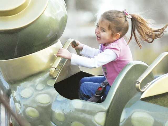 Briell Dobreff, 4, rides the Alligator Alley roller coaster at the Christiansen Amusements carnival Saturday at Westfield Valencia Town Center.