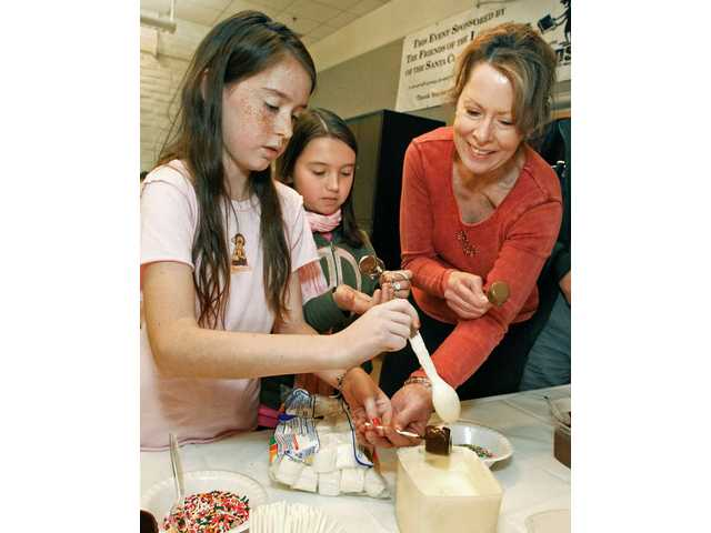 From left, Julia Thibodeaux, 10, Lauren Santilli, 10, and Carolyn Thibodeaux,  make chocolate-covered marshmallows.
