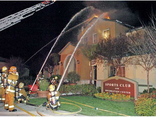Firefighters battle a blaze erupting from the roof of the sports recreation center at the Promenade Apartments at Town Center in Valencia that started at about 10:30 p.m.Saturday.