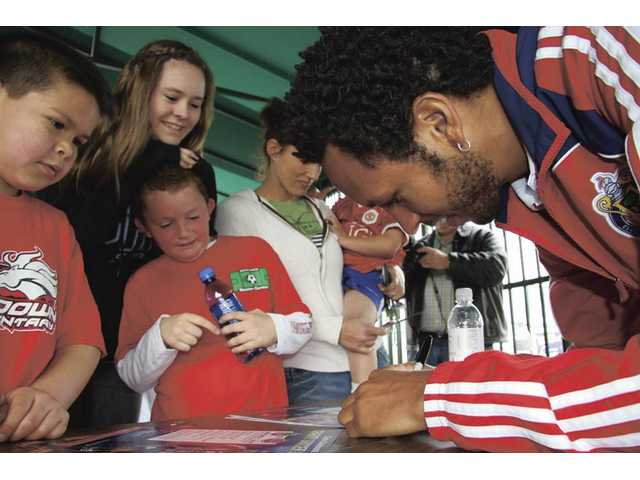 Lawson Vaughn signs autographs for a group of kids at the Santa Clarita Soccer Center Sunday.