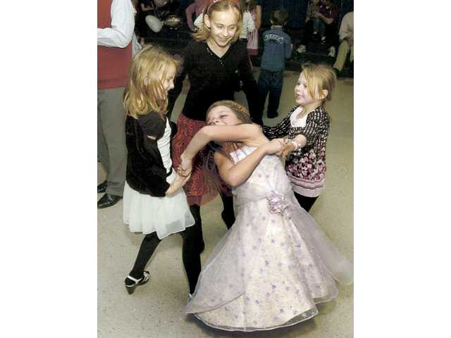 Brooke Hougo, front, is spun by second grade classmates Kaela Berretta, left, Lucy O'Brien and Hailey Bertran, right, as they dance at the Cupid's Ball.