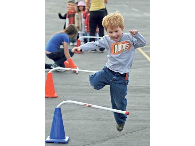 Nigel Shirley, a kindergarten student at Meadows Elementary School, jumps a hurdle during the school's triathlon fundraiser. The school's student council and PTA organized the event.