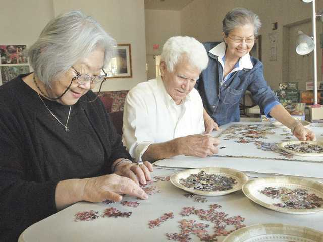"From left, Dolores Saracho, Jose Bellas and Gloria Pasco join forces as they work on a 1,000 piece jigsaw puzzle entitled ""Grandpa Watches the Kids"" at the Bouquet Canyon Apartments on Thursday."