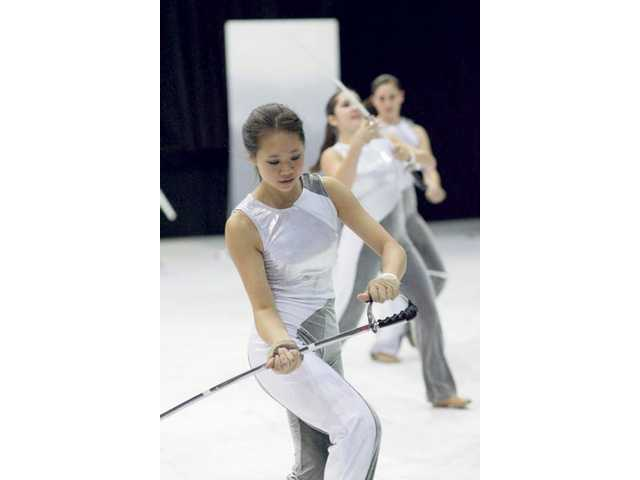 Kate Wong practices with Valencia High School's Colorguard, which hopes to raise $15,000 — enough to take the team to the World Championships in Ohio in April.