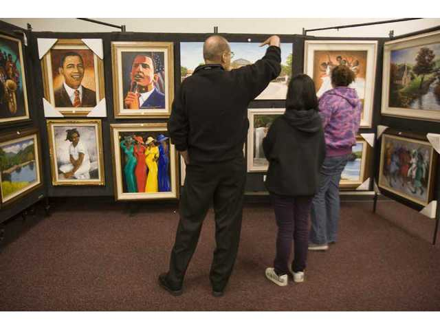 Michael R. Powell, left, and his daughters Kenna and Tiana look over artwork by local artist Romeo Downer at the African American display at Hart Hall last weekend.