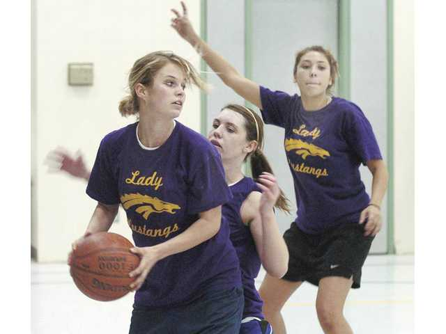From left, Rachelle Beaudoin backs in teammate Christy Lundin as Sylvia Escobedo calls for a pass during the Vasquez High girls basketball team's practice in Acton on Tuesday. Vasquez will play a CIF-Southern Section playoff game for the first time in school history on Thursday.