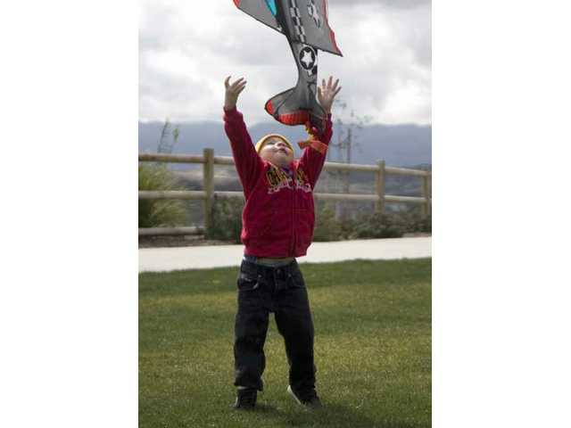 Two-year-old Steven Sorrow, of Canyon Country, launches a kite at Todd Longshore Park Tuesday afternoon.