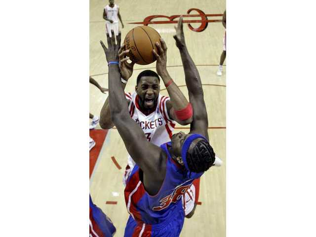 This Dec. 15, 2009, file photo shows Houston Rockets' Tracy McGrady (3) being fouled by Detroit Pistons' Kwame Brown (38) during the first quarter of an NBA basketball game in Houston. Published reports say the Houston Rockets have traded McGrady and his massive expiring contract to the Sacramento Kings for guards Kevin Martin and Sergio Rodriguez, center Hilton Armstrong and forward Kenny Thomas.