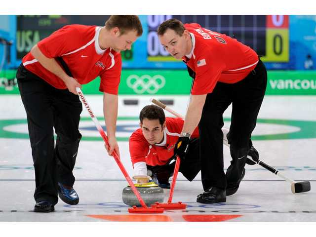 America's Jason Smith, center, delivers the stone for sweepers, Jeff Isaacson, left, and Jason Smith in men's curling at the Vancouver 2010 Olympics in Vancouver, British Columbia, Friday, Feb. 19, 2010.
