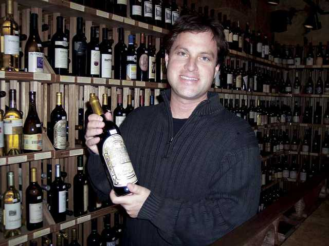 David Schutz, owner of All Corked Up, displays one of the bottles of wine available at the wine bar located in Centre Pointe in Santa Clarita. All Corked Up has expanded to offer a full meal service.