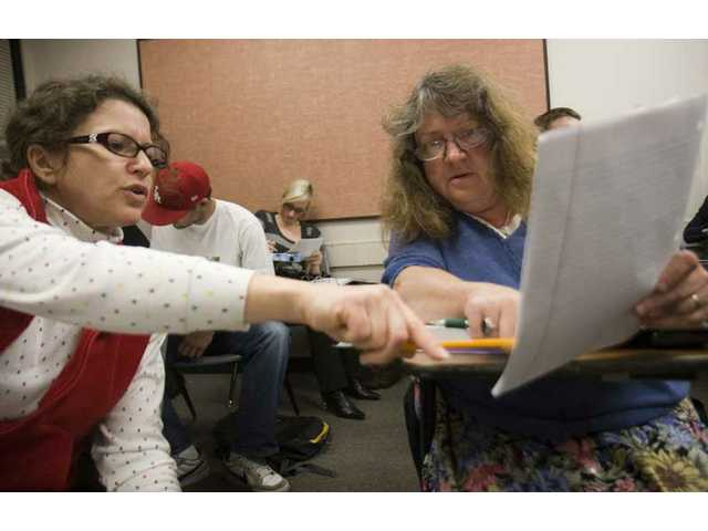 Classmates Marcia Holtz, left, and Beverly Axen, right, from Valencia, go over their math homework during their Intro to Statistics class at College of the Canyon Wednesday evening.
