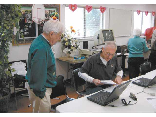 Jim Ozasky, right, helps Ben Placek organize his income tax forms at the SCV Senior Center on Feb. 21.
